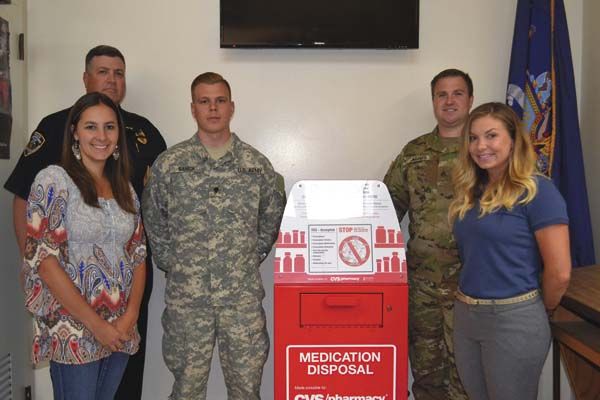 From left, mayor's assistant Rachel Frasier, Police Chief Marc Porter, National Guard Specialist Joshua Banick, Sgt. Anthony Adams and Master Sgt. Jessica Ramirez stand by the new drug drop box at the Gloversville Police Station on Friday.  (The Leader-Herald/Kerry Minor)