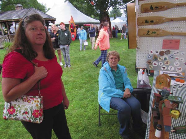 Lisa Benesh visits her mother-in-law  Sharon Benesh and father,  Joseph (not shown), both of Holland Patent at their booth containing model vehicles and other woodworking. (The Leader-Herald/Eric Retzlaff)