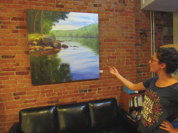 "Gianna DeLilli, general manager of the Mohawk Harvest Copperative on Main Street, points out ""Summer Light,"" her favorite painting by featured artist Takeyck Walter on display at the Micropolis in the coop during Friday's Gloversville Twilight Market. (The Leader-Herald/Eric Retzlaff)"