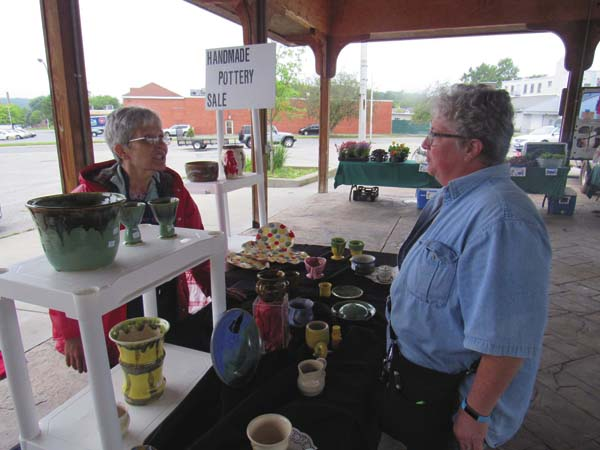 Jeanne Teetz of Gloversville, right, chats with Christine Wagoner of Johnstown at Wagoner's Peace of Pottery both at the Gloversville Twilight Market Friday at the Farmers Market Pavilion. (The Leader-Herald/Eric Retzlaff)