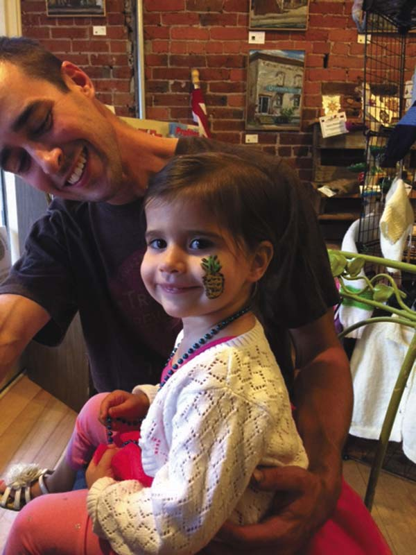 Chris Ioele holds his daughter Laurel on his lap after Janelle Krause painted pineapple on her cheek at the Mohawk Harvest Cooperative Market. (Photo submitted)