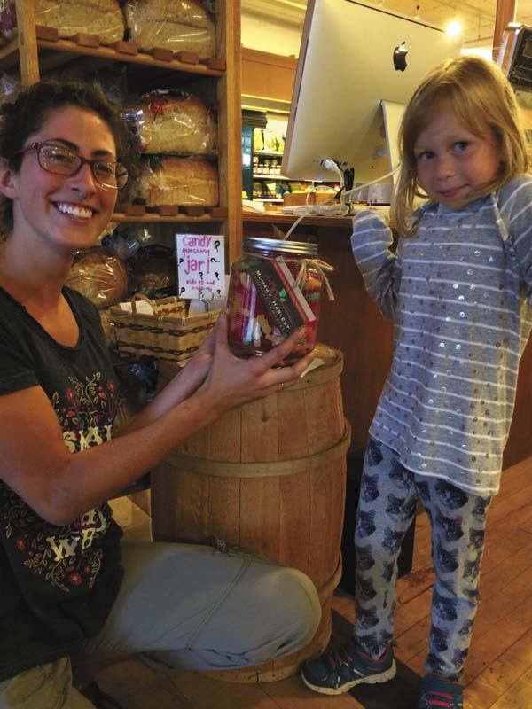 Gianna DeLilli, general manager of the Mohawk Harvest Cooperative Market, asks Alice Tomchik of Johnstown to guess the number of jellies in the jar. (Photo submitted)
