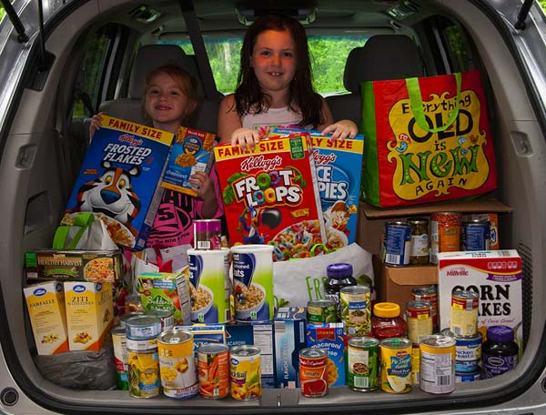 Shown, from left, are Aurora Horne and her sister, Isabella, with some of the food donated by the guests at Aurora's sixth birthday party. (Photo submitted)