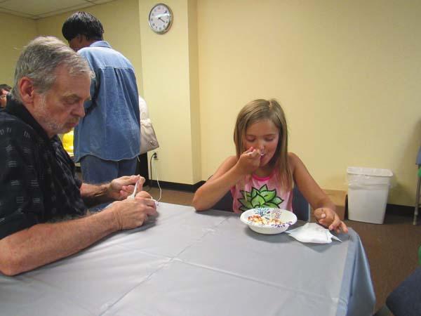Brian Conroy of Gloversville accompanies his niece Alana McDonald, 8, of Broadalbin at a Gloversville Public Library summer reading program ice cream social. (The Leader-Herald/Eric Retzlaff)