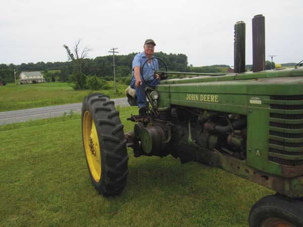 Richard Aesch of Mayfield pulls up in a still-functioning 1941 John Deere Tractor that his father, Alex, used for farm work from 1953 to 1972 on Saturday at the Coon Hollow Engine and Tractor Show at the K.C. Canary building on Route 29 in Mayfield. (The Leader-Herald/Eric Retzlaff)