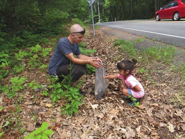 Rachael Taback, right, helps her dad, Justin Taback clean up trash thrown alongside the road. (Photo submitted)