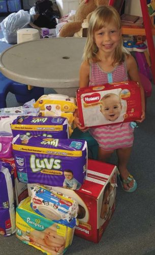 Alice Tomchik of Johnstown gives packages of diapers to No Bottom Left Behind Diaper Bank, 530 N. Perry St. She asked guests at her seventh birthday party to donate diapers to help babies rather than bringing gifts for her. (Phot0 submitted)