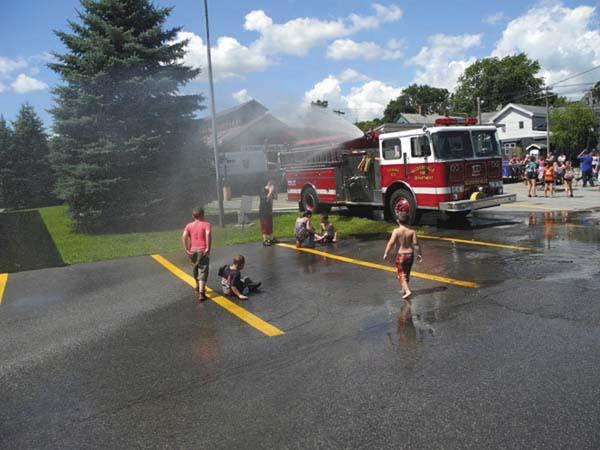 Kids cool off in the spray from a Gloversville Fire Department firetruck during 2016's Rail Fest. (Eric Retzlaff)