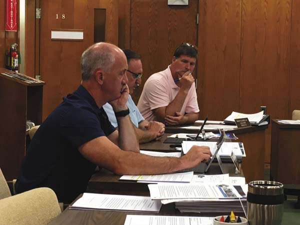 From the foreground backward, District 2 Legislator Brian Sweet, Legislature Chairman Roy Dimond and District 4 Legislator Robert Headwell Jr. discuss funding for Fonda Fair Youth Days Tuesday night. (The Leader-Herald/Jason Subik)