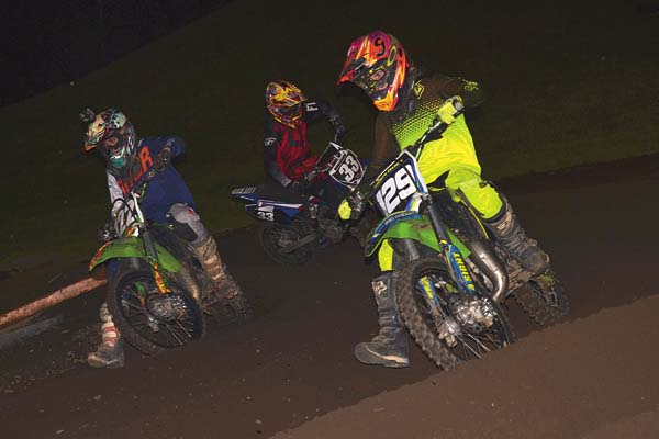 Carter Petersen (122), Hayden Zelich (129) and Deegan Thrasher (33) race through a turn in an open mini 10-to-16-year-old moto during STR/Monster Energy Supercross competition Wednesday at Royal Mountain Ski Area in Caroga Lake. (The Leader-Herald/Paul Wager)