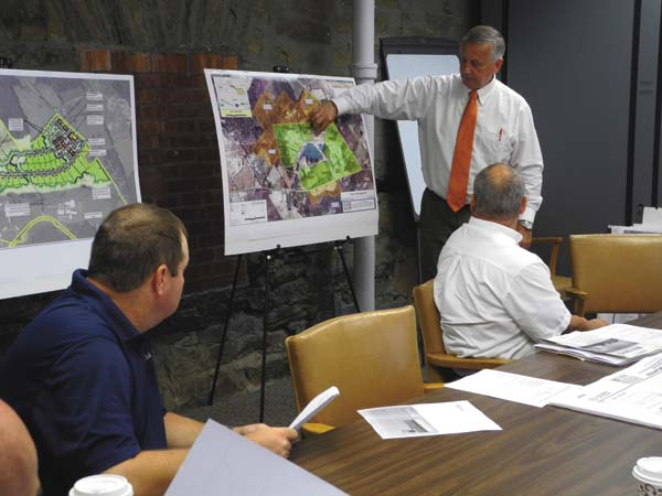 Fulton County Industrial Development Agency Executive Director James Mraz, standing, shows maps of the Tryon Technology Park to the IDA board Thursday at the Fort Johnstown Annex. Left and right are board members William Sullivan and Todd Rulison. (The Leader-Herald/Michael Anich)