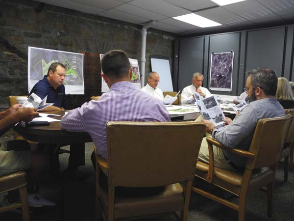 Members of the Fulton County Industrial Development Agency board review Fulton County's new newsletter Tuesday at the Fort Johnstown Annex in Johnstown. (The Leader-Herald/Michae Anich)