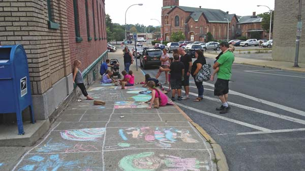 Children participate in the chalk art contest as part of the Twilight Market Friday evening.  (The Leader-Herald/Kerry Minor)
