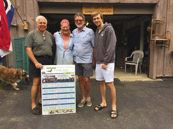 Rick Ruby, Shawn Cleland, Peter Kiernan and Kyle Price look display the Caroga Lake Music Festival season schedule at Timberlane Blueberry Farm. (Photo submitted)