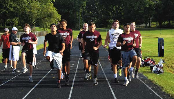 "William ""Buck"" Galster, black shirt, Jared Malagisi, center and Zach Alikhan lead members of the Gloversville Huskies through stretches as they prepare for practice on the first day of the fall high school sports season today at Park Terrace Elementary School. (The Leader-Herald/James A. Ellis)"