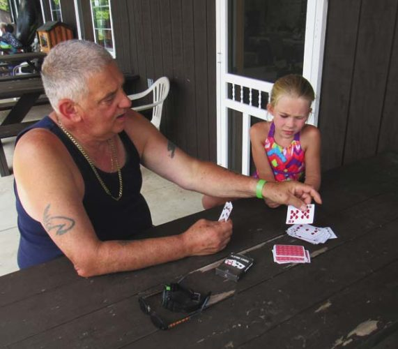 John Ginna plays cards with his granddaughter Sophia, 6, both of the Catskills, during the 100th anniversary gathering Saturday of the East Caroga Lake Environmental Association. (The Leader-Herald/Eric Retzlaff)