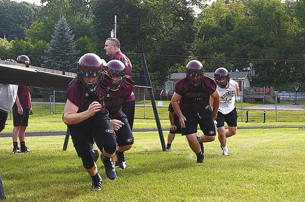 Gloversville head coach Jared Bongo, center, works a drill with the Huskies linemen during the opening day of practice for the 2017 season Monday at  Park Terrace Elementary School. (The Leader-Herald/James A. Ellis)