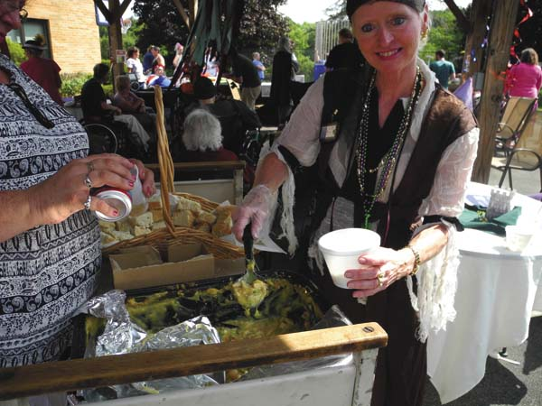Activities aide Debbie Rivenburgh serves up some food at the Fulton Center for Rehabilitation and Healthcare's Renaissance Fair Wednesday in the town of Johnstown. (The Leader-Herald/Michael Anich)