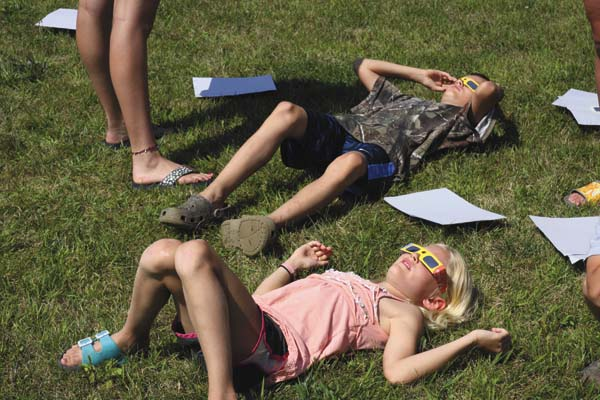 Abigail Lozier, 6, and Tyler Lozier, 10, both of Palatine Bridge, look at the sun while laying on the lawn at Arkell Museum and Canajoharie Library Monday. (The Leader-Herald/Patricia Older)