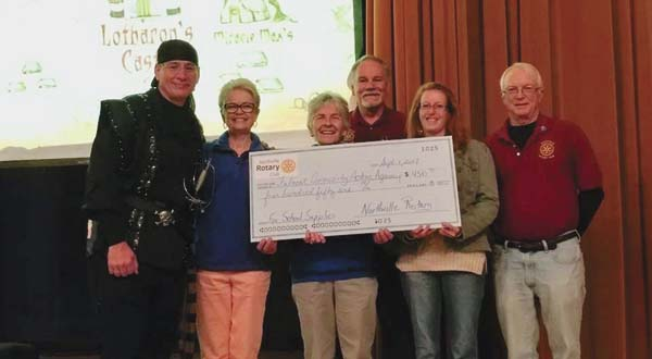 "Rotary President Ken Adamczyk (dressed as his favorite ""Princess Bride"" character),  Rotarians Mike Kratky and Chas Owens present the check to Vanessa Carey, Center Coordinator of the Fulmont Community Action Agency in Northville.  Dr.  Leslie Ford, Superintendent and Arlene Rambush, board member of Northville Schools assisted. (Photo submitted)"