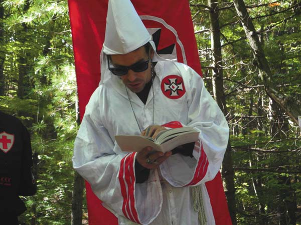 Gary Munker of the Loyal White Knights of the Klu Klux Klan reads a passage about Jews from the King James Bible during a recent interview in a Gloversville woods. (The Leader-Herald/Michael Anich)