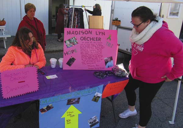 Friends of Madison Oechler, from left in foreground, Abby McNamara and Brandi Hirschheld, and Brandi's grandmother, Donna Hirscheld, all of Amsterdam, work at a table collecting donations and selling bracelets Friday at the Fulton County Fall Festival in Gloversville, a fundraiser for Oechler. (The Leader-Herald/Eric Retzlaff)