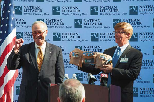 U.S. Senate Minority Leader Charles Schumer gestures in support of the tool belt given to him by Nathan Littauer Hospital and Nursing Home filled with energy bars for all the work ahead of him. Holding the tool belt is Laurence Kelly, CEO and president of Littauer. (Photo submitted)