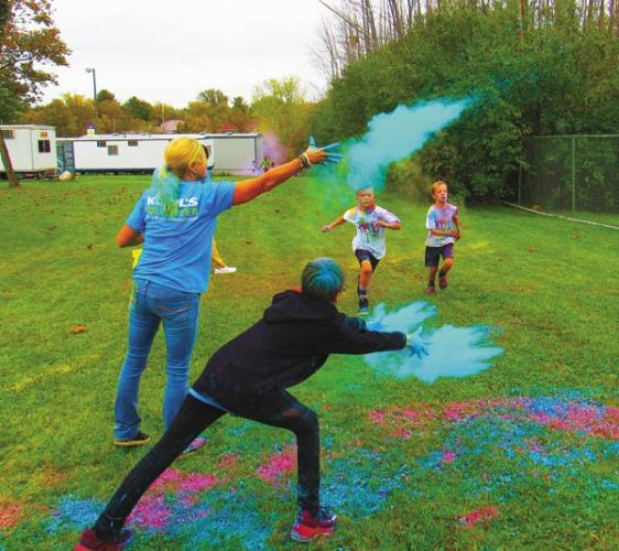 Finishers run the gauntlet of colored powder at the 3K Color Run/Walk fundraiser Saturday, sponsored by the Johnstown elementary schools Parent-Teacher Association. (The Leader-Herald/Eric Retzlaff)