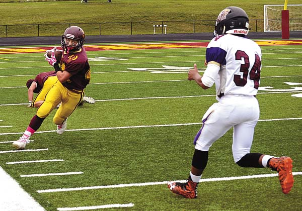 Holy Trinity's Nelon Priest (34) closes in on Fonda-Fultonville's Jon Flander as he turns up field after catching a pass from quarterback John Mancini during Saturday's game at John G. Boshart Field at Fonda-Fultonville High School. (The Leader-Herald/James A. Ellis)