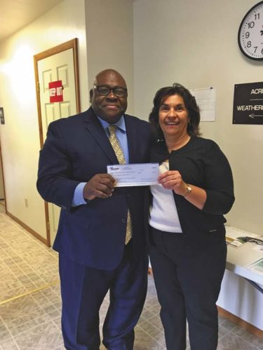 NBT Bank Affordable Housing Originator Al Wells and Albany County Rural Housing Alliance Executive Director Judith Eisgruber are shown with a $1,000 check to the Albany County Rural Housing Alliance, Inc. on Aug. 28 as part of NBT Bank's Home in the City Program in Amsterdam, Gloversville and Johnstown. (Photo submitted)