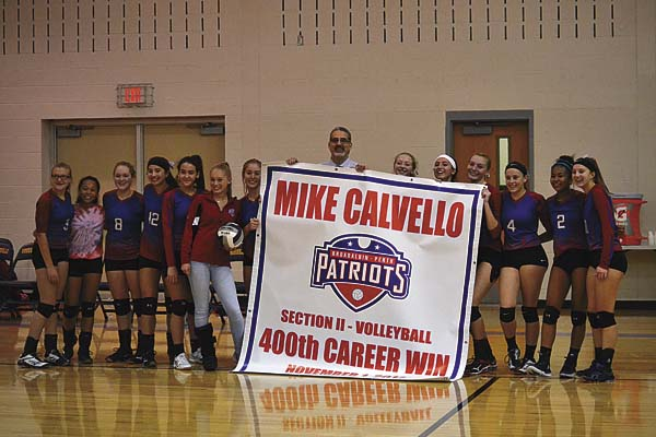 The Broadalbin-Perth volleyball team poses with coach Mike Calvello after his won his 400th career match Wednesday. The Lady Patriots posted a 3-0 victory over Holy Names in the Section II Class B semifinals at Voorheesville High School. (The Leader-Herald/Paul Wager)