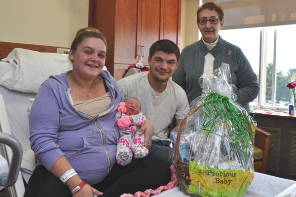 Meagan Fleaszar and Austin Syzdek with newborn daughter Sophia Syzdek are shown with Jean LaPorta, president of Friends of the Gloversville Public Library, which donated a basket of books and gifts to the couple during National Friends of Libraries Week in October. (Photo submitted)