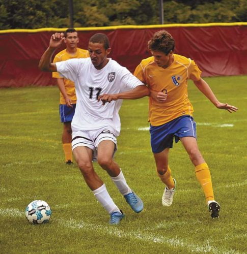 Gloversville's Marwan Abbas (17) is pressured by Queensbury's Matt Ricciardelli during a Foothills Council match Aug. 29 at Husky Field. Abbas recently was named a first-team Foothills Council all-star. (The Leader-Herald/James A. Ellis)
