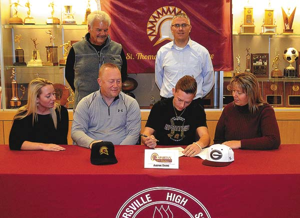 Gloversville's Aaron Dona, center, signs his Letter of Intent to attend and play baseball for NCAA Div. II St. Thomas Aquinas College Friday at Gloversville High School. Looking on are his sister Ashley, father Thom and mother Ronnie along with Gloversville High School baseball coaches Mike Ponticello and Mike DeMagistris. (The Leader-Herald/James A. Ellis)