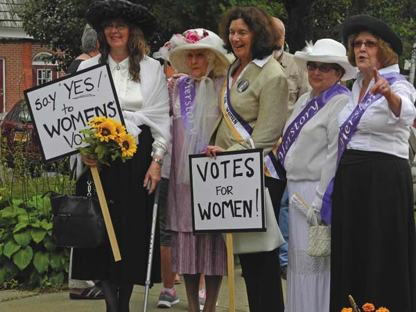 Women dressed in period garb hold signs during a downtown Johnstown ceremony last August honoring Elizabeth Cady Stanton. (The Leader-Herald/Michael Anich)