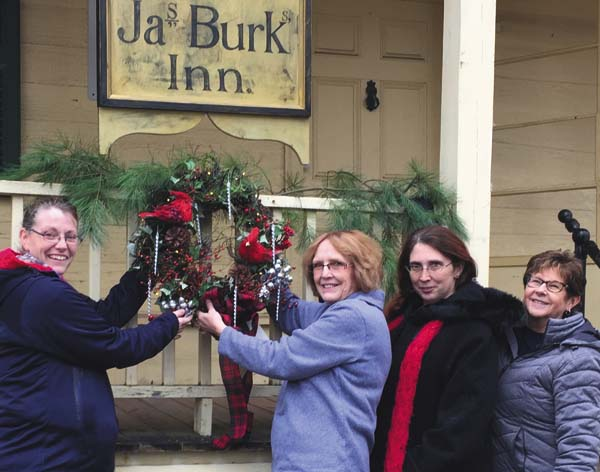From Left: Hollie King, Helen Martin, Bernadette Weaver and Cathy VanAlstyne prepare to hang one of the donated wreathes that will be available for purchase at the Johnstown Historical Society's Festival of Wreaths on November 25 at the James Burk Inn, Johnstown. (Photo Submitted)