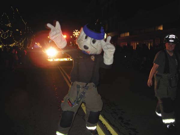 A firefighting character dances along the Johnstown Holiday Parade route Friday night. (The Leader-Herald/Michael Anich)