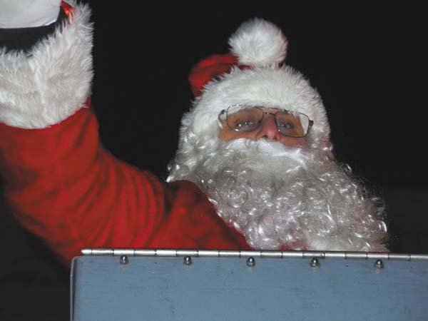 Santa Claus waves to a crowd from a fire truck concluding the Holiday Parade Friday night in downtown Johnstown. (The Leader-Herald/Michael Anich)