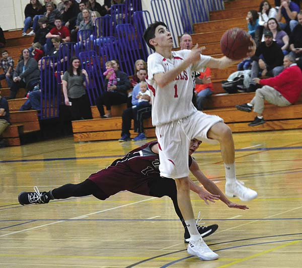 Wells' Justin Foster (1) drives past Fort Plain's Jacob Hisert during Friday's Coaches vs. Cancer Tip-Off Classic game at Fulton-Montgomery Community College in Johnstown. (The Leader-Herald/Paul Wager)