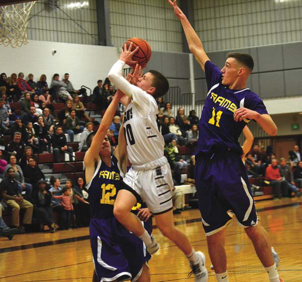 Gloversville's Dante Bouchard, center, drives to the basket as Amsterdam's Jeff Brennan (12) and Louis Fedullo (11) defend during Friday's Foothills Council South Division game at Gloversville High School. (The Leader-Herald/Paul Wager)