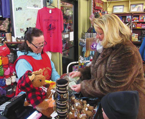 Elayne Wade, manager of Northville 5 and 10 Cent Store, left, sells gloves to Sherrie Fonda of Mayfield for her grandson Garrett Sieg, 5, before the Northville Christmas parade Saturday afternoon. It was one of many downtown businesses busy with customers. (The Leader-Herald/Eric Retzlaff)