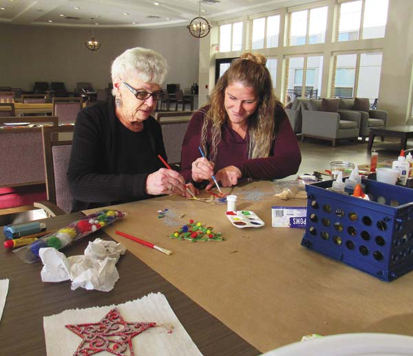 At right, Amanda Campione, activities director of The Sentinel of Amsterdam, a new assisted living facilities on Market Street, works on a craft with facility resident Pat Seeley, formerly of Broadalbin. (The Leader-Herald/Eric Retzlaff)