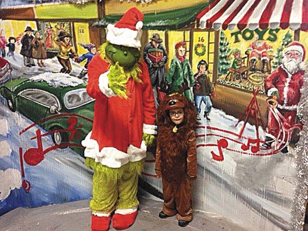 """Zach Byrns as the Grinch and Lorenzo Boles as Max, his dog, pose in front of a backdrop for """"How the Grinch Found Christ in Christmas"""" at North Main Street United Methodist Church in Gloversville. The audience-participation play will be produced at 10:30 a.m., Sunday Dec. 10. The public is invited to attend. (Photo submitted)"""