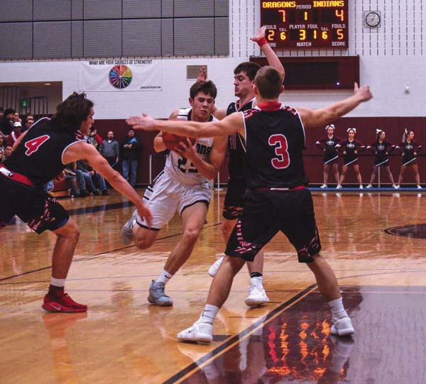 Gloversville's Joey Rowback (23) is boxed in by Glens Falls' David Barclay (4), Noah Balcom and Joe Girard III as he drives to the hoop during the first quarter of Tuesday's Foothills Council game at Gloversville High School. (The Leader-Herald/James A. Ellis)