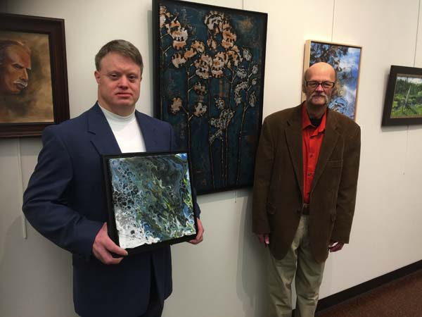 Francis Dempsey and Richard Freeman pose with their artwork at the opening reception of The Art of New York: Annual Juried Art Show hosted by the Arkell Museum and Canajoharie Library. (Photo submitted)