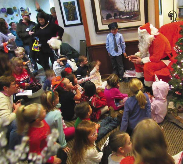 Santa Claus chats with children during the Polar Express Celebration Saturday at the Paul Nigra Center for Creative Arts in Gloversville. (The Leader-Herald/Eric Retzlaff)