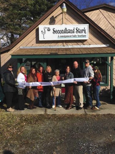 Owner Lisa Rougier (with scissors) and her husband, Josh, on her left, cut the ribbon with family and friends; chamber ambassador Jenny Rulison-Fisch (State Farm Insurance) is at far left. (Photo submitted)