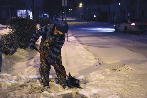 Amber Chamberlain shovels snow Friday morning at the corner of Freemont and Washington streets. (The Leader-Herald/Patricia Older)