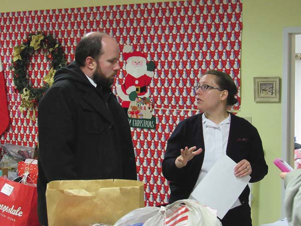Lts. Mark and Ann Marie Devanney of The Salvation Army of Fulton County go over details of the Toy Drive pick up at the Gloversville Senior Center on Thursday. (The Leader-Herald/Kerry Minor)