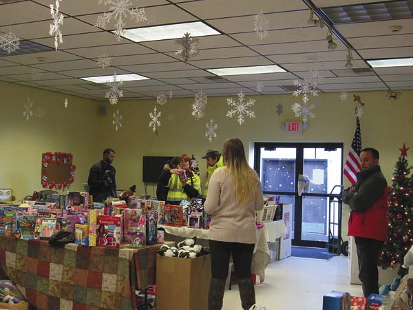 Shoppers and volunteers make their way through the toy pick. (The Leader-Herald/Kerry Minor)